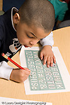 Education Preschool 3-4 year olds boy writing letters and numbers using stencil vertical
