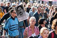 """Etwa 2.000 Menschen demonstrierten am Mittwoch den 11. Juli 2018 in Berlin unter dem Motto """"Kein Schlussstrich - Das Problem heisst Rassismus"""" anlaesslich der Urteilsverkuendung im Muenchner NSU-Prozess. In Redebeitraegen, auf Plakaten und Transparenten wurde die Nicht-Aufklaerung der Terrororganisation """"Nationalsozialistischer Untergund"""" - NSU - kritisiert. So hat die Staatsanwaltschaft im ueber fuenf Jahre dauernden Prozess immer von drei Personen gesprochen, die den NSU gebildet haben sollen, obwohl im Verfahren klar geworden ist, dass der NSU mit seinem Netzwerk aus mind. 50 Personen bestehen muss. Auch wurden die geringen Strafen gegen einige der Angeklagten kritisiert.<br /> Die Demonstration wurde von vier Einsatzhundertschaften der Berliner Polizei begleitet und ueber einem dutzend ziviler Staatschutzbeamten beobachtet.<br /> Im Bild: Eine Demonstrationsteilnehmerin haelt ein Portrai von Enver Simsek, der am 9. September 2000 in Nuernberg vom NSU ermordet wurde.<br /> 11.7.2018, Berlin<br /> Copyright: Christian-Ditsch.de<br /> [Inhaltsveraendernde Manipulation des Fotos nur nach ausdruecklicher Genehmigung des Fotografen. Vereinbarungen ueber Abtretung von Persoenlichkeitsrechten/Model Release der abgebildeten Person/Personen liegen nicht vor. NO MODEL RELEASE! Nur fuer Redaktionelle Zwecke. Don't publish without copyright Christian-Ditsch.de, Veroeffentlichung nur mit Fotografennennung, sowie gegen Honorar, MwSt. und Beleg. Konto: I N G - D i B a, IBAN DE58500105175400192269, BIC INGDDEFFXXX, Kontakt: post@christian-ditsch.de<br /> Bei der Bearbeitung der Dateiinformationen darf die Urheberkennzeichnung in den EXIF- und  IPTC-Daten nicht entfernt werden, diese sind in digitalen Medien nach §95c UrhG rechtlich geschuetzt. Der Urhebervermerk wird gemaess §13 UrhG verlangt.]"""