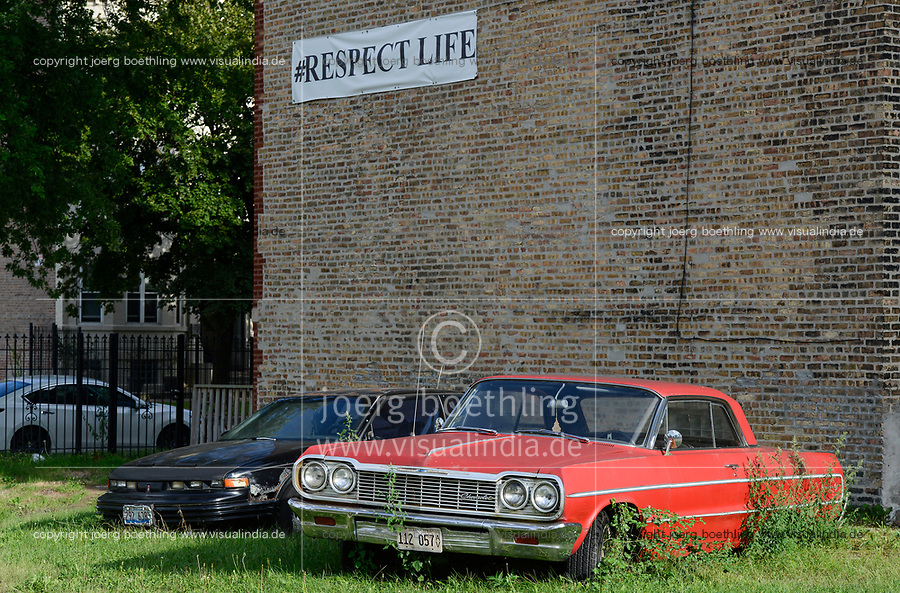 USA Chicago, south side of Chicago, Washington Park, afroamerican quarter with violence and criminal youth gangs , red cadillac car and hashtag respect life / afroamerikanisches Viertel mit Jugendgangs und hoher Kriminalitaet, chevrolet und Hauswand mit Banner #Respect Life