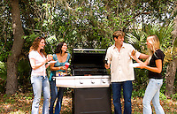 Group of mixed ethnic friends in their 20s having fun at home barbaguing in yard outdoors having fun and laughing