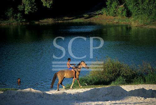 Salvador, Bahia State, Brazil. Young man riding bareback on a horse, man swimming; Lagoa de Abaete.