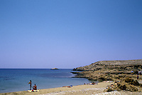 Sunbathers along the unpopoulated shores of Ios, Greece.
