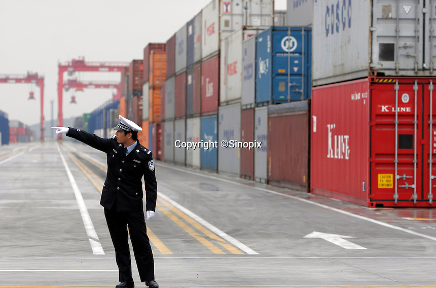 A police officer directs traffic at the opening of the Yangshan Deep Water Port in Shanghai, China. The port will give the city it's first deep water port, adding capacity to its formidable shipping infrastructure, already Shanghai is expected to become world's largest freight port at the end of this year surpassing Singapore, according to materials provided by the Ministry of Commerce..