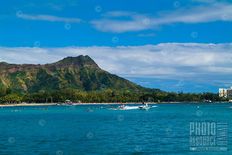 Majestic Diamond Head and the green coastline by Kapiolani Park shot from a sailboat on the clear blue water off Waikiki.