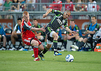 Seattle Sounders FC midfielder Osvaldo Alonso #6 and Toronto FC defender Richard Eckersley #27 in action  during an MLS game between the Seattle Sounders FC and the Toronto FC at BMO Field in Toronto on June 18, 2011..The Seattle Sounders FC won 1-0.