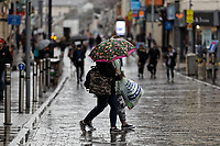 Pictured: Shoppers walk in the rain in Oxford Street, Swansea, a day before storm Dennis is due to affect parts of the country. Friday 14 February 2020