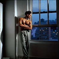 Shirtless African American man standing with nighttime city windows as background<br />