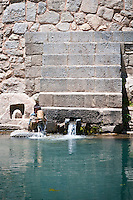 A young boy rinses a jug at the spring at the Naranag Temple Complex, This is one of the largest temple complexes in Kashmir. It dates from the 9th Century AD. The chief deity is Lord Shiva.  Kashmir, India