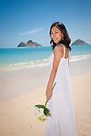 Asian bride glances over her shoulder with bouquet of flowers on Lanikai beach. Mokulua Islands in background.