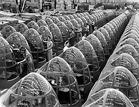Stars over Berlin and Tokyo will soon replace these factory lights reflected in the noses of planes at Douglas Aircraft's Long Beach, Calif., plant.  Women workers groom lines of transparent noses for deadly A-20 attack bombers.  October 1942.  Alfred Palmer.  (OWI)<br /> Exact Date Shot Unknown<br /> NARA FILE #:  208-AA-352QQ-5<br /> WAR & CONFLICT BOOK #:  802