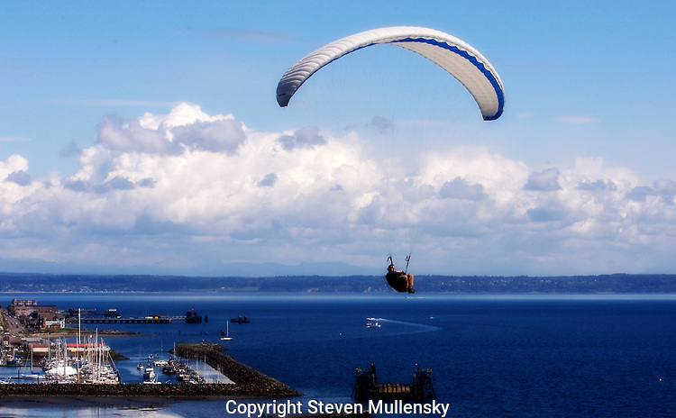 A paraglider soars along the bluffs overlooking Port Townsend Bay.