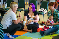 """Breastfeeding a newly arrived baby at a singing and signing group whilst talking to the other mothers.Image from the breastfeeding collection of the """"We Do It In Public"""" documentary photography picture library project: <br />  www.breastfeedinginpublic.co.uk<br /> <br /> <br /> Berkshire, England, UK<br /> 27/09/2013<br /> <br /> © Paul Carter / wdiip.co.uk"""