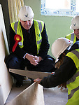 © Joel Goodman - 07973 332324 .  04/02/2014 . Manchester , UK . Ed Balls and Mike Kane watch as apprentice joiner saws chipboard . Ed Balls , MP for Morley and Outwood and Shadow Chancellor of the Exchequer the Labour Party , joins Labour candidate Mike Kane on the campaign trail ahead of the Wythenshawe and Sale East by-election , following the death of MP Paul Goggins . They visit apprentices at the Leybrook Road building site in Wythenshawe where apprentice builders work on bungalows built for affordable rent . Photo credit : Joel Goodman