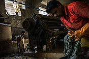 Workers process raw hides on a frizing machine as others collect the sludge byproduct in a drainage pit at a tannery in the Bantala area of Kolkata, West Bengal, India.