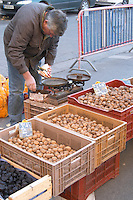 Walnuts and dried plums for sale at a market stall at the market in Bergerac. A man selling the walnuts with a very oldfashioned scale Bergerac Dordogne France