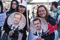 """250 bis 300 Menschen demonstrierten am Samstag den 31. Oktober 2015 in Berlin fuer die Unterstuetzung des syrischen Diktators Assad durch Russland. Sie trugen Fahnen Syriens, der ehemaligen Sowietunion, Russlands, Nordkoreas, der DDR, des Iran und Venezuelas, die sich """"alle zusammen gegen den Imperialismus zur Wehr setzen"""" wuerden. Russlands Praesident Putin wurde ausdruecklich fuer sein Militaerengagement gedankt, das Eingreifen der USA verurteilt.<br /> Im Bild: Demonstrantinnen mit Portraitfotos des syrischen Diktators Assad.<br /> 31.10.2015, Berlin<br /> Copyright: Christian-Ditsch.de<br /> [Inhaltsveraendernde Manipulation des Fotos nur nach ausdruecklicher Genehmigung des Fotografen. Vereinbarungen ueber Abtretung von Persoenlichkeitsrechten/Model Release der abgebildeten Person/Personen liegen nicht vor. NO MODEL RELEASE! Nur fuer Redaktionelle Zwecke. Don't publish without copyright Christian-Ditsch.de, Veroeffentlichung nur mit Fotografennennung, sowie gegen Honorar, MwSt. und Beleg. Konto: I N G - D i B a, IBAN DE58500105175400192269, BIC INGDDEFFXXX, Kontakt: post@christian-ditsch.de<br /> Bei der Bearbeitung der Dateiinformationen darf die Urheberkennzeichnung in den EXIF- und  IPTC-Daten nicht entfernt werden, diese sind in digitalen Medien nach §95c UrhG rechtlich geschuetzt. Der Urhebervermerk wird gemaess §13 UrhG verlangt.]"""