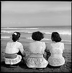 On Bali's east coast a few young women stare at the ocean during a religious ceremony. For the Balinese different spirits live in the mountains, on land and in the ocean. The girls are sitting on their flip flaps. Flip flaps are cheap and used instead of more expensive shoes.