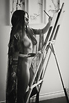 Beautiful young woman sumi-e artist with an easel painting naked in her home studio Black and white portrait Image © MaximImages, License at https://www.maximimages.com