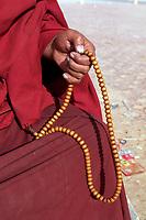 A Tibetan monk holding prayer beads in the thangka artists village, Upper Wutan Monastery, Rebgong (Chinese name - Tongren),  on the Qinghai-Tibetan Plateau. China.