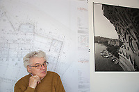 """Switzerland. Canton Ticino. Mendrisio. The architect Mario Botta in his office. On the wall, rolls of blueprints with architectural plans and technical drawings of the """"Thermalbad"""" in Baden, Switzerland. A black and white picture from the San Carlino, built by Mario Botta in 1999  to celebrate the 400th anniversary of the birth of the architect Francesco Borromini. Standing almost 33 meters high and made up of 35,000 planks each 4,5 cm thick, mounted modularly with a """"separation"""" of 1 cm, the large wooden model of San Carlino was held together with steel cables, in turn fixed to a steel frame weighing 90 tonnes. This life-size cross-section view of the church sat on a 22 square-meters platform just a few meters from the shore, at the end of the lake promenade and at the entrance to the Parco Ciani. The wooden model of San Carlino thus emerged from the deepest inlet of the lake gulf to act as a signpost to the exhibition about the young Borromini. 30.10.2017 © 2017 Didier Ruef"""