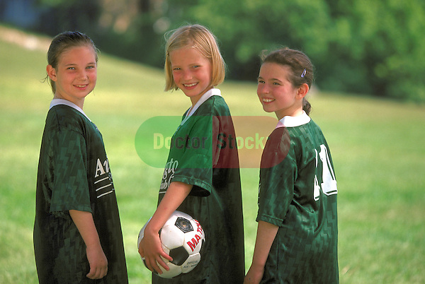 portrait of three smiling girls in uniform with soccer ball