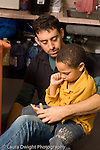 Preschool 3-5 year olds male teacher sitting with unhappy boy after conflict with another child teacher working to resolve situation vertical