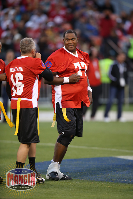SAN FRANCISCO, CA - JULY 12:  Former San Francisco 49ers great Bubba Paris stands in the huddle with Joe Montana during the Legends of Candlestick flag football game at Candlestick Park in San Francisco, California on July 12, 2014. Photo by Brad Mangin