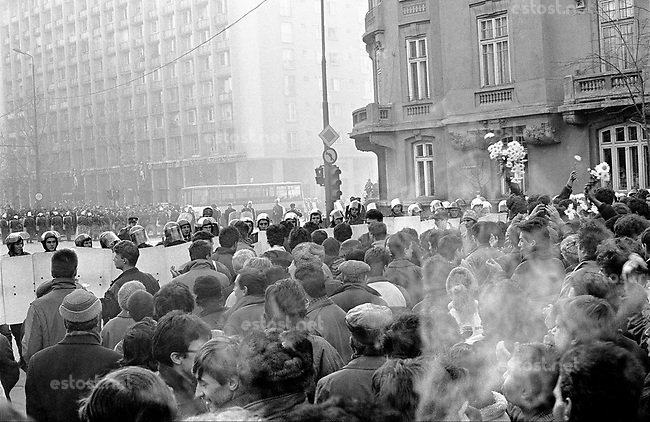 ROMANIA, Bd. Magheru, Bucharest, 21.12.1989.People rise against Ceausescu. To show that they are peaceful they offer flowers to the policemen. An armoured army vehicle is visible in the background to the far right. Seconds later it will drive into the crowd. Hundreds were left dead and wounded that night..© Andrei Pandele / EST&OST
