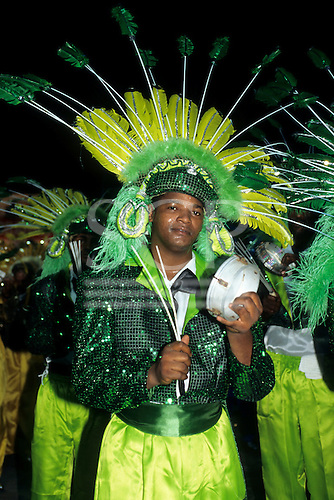 Rio de Janeiro, Brazil. Carnival; young man playing a pandeiro (small hand drum), in a yellow and green costume.