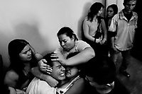 A Colombian boy, held by his fellow believers, screams of pain while being allegedly possessed by demons during the exorcism ritual performed at a house church in Bogota, Colombia, 28 January 2013. Hundreds of Christian belivers, joined in nameless groups, gather every week in unmarked home churches dispersed in the city outskirts, to carry out prayers of liberation and exorcism. Community members and their religious activities are usually conducted by a charismatic pastor or preacher. Using either non-contactive methods (reading religous formulas from bible, displaying Christian symbols and icons) or rough body-pressure-points techniques and forced burping, a leading pastor commands the supposed evil spirit, which is generally believed to come from witchcraft, to depart a person's mind and body. The demon's expulsion often consists of multiple rites and may last for several months.