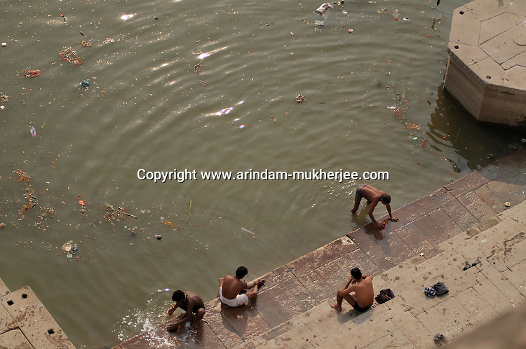 Indian people using polluted and dirty water of river Ganga for bathing and washing cloths, Uttar Pradesh, India.