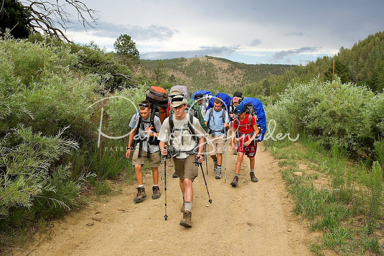 Photo story of Philmont Scout Ranch in Cimarron, New Mexico, taken during a Boy Scout Troop backpack trip in the summer of 2013. Photo is part of a comprehensive picture package which shows in-depth photography of a BSA Ventures crew on a trek.  In this photo BSA Venture Crew Scouts make their way down a trail against the backdrop of the mountains in the backcountry at Philmont Scout Ranch.   <br /> <br /> The  Photo by travel photograph: PatrickschneiderPhoto.com