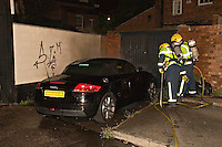 Audi TT alight being extinguished by firefighters wearing BA Warwickshire UK. This image may only be used to portray the subject in a positive manner..©shoutpictures.com..john@shoutpictures.com