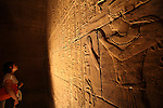 A visitor looking at the stone carvings inside of the Ramesseum Temple. Luxor. Egypt