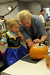London Ryba, 2, and her mother Marcie Ryba create some Halloween art at the Carson City Library Monday, Oct. 27, 2014. As part of the library's Halloween festivities, dozens of children decorated pumpkins or gourds and took part in a costume contest.