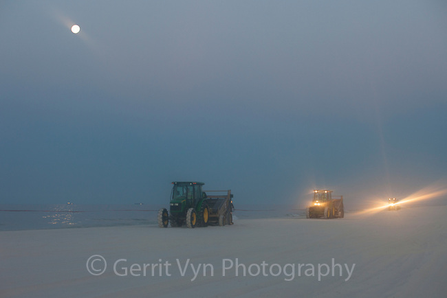 Oil spill response vehicles grooming a white sand beach before sunrise. Many clean up efforts from the BP Deepwater Horizon oil leak were cosmetic in nature and aimed to cover up the damage. These vehicles covered up contaminated sand with clean sand throughout the night. Bon Secour National Wildlife Refuge, Baldwin County, Alabama. June 2010.