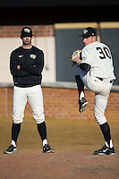 Aaron Fossas (left) watches Rayne Supple (30) warm-up in the bullpen during the game against the Richmond Spiders at David F. Couch Ballpark on March 6, 2016 in Winston-Salem, North Carolina.  The Demon Deacons defeated the Spiders 17-4.  (Brian Westerholt/Four Seam Images)