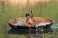 INDIA Karnataka , fishing nomads, girl with boat on river Phalguni / INDIEN Karnataka Moodbidri , Fischer Familien mit ihren Kindern am Fluss Phalguni, Maedchen in einem Boot mit bespannter Tierhaut