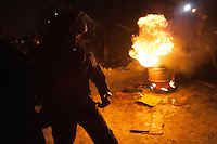 A police officer seen during the nightly assault on barricades occupying the government district in Kiev. Ukraine