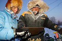 Volunteer Sally Hamm checks in frozen Jeff King @ Ruby Chkpt -30 temps Ruby Alaska Interior Winter
