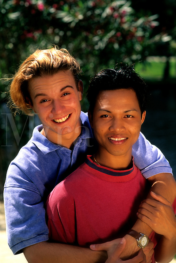 Portrait of a happy affluent gay male couple snuggling on a beautiful sunny day at home