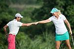 Xing Aowei (pink pants) and Anna Nordqvist (green skirt) bump fists at the end of their game during the World Celebrity Pro-Am 2016 Mission Hills China Golf Tournament on 23 October 2016, in Haikou, Hainan province, China. Photo by Weixiang Lim / Power Sport Images