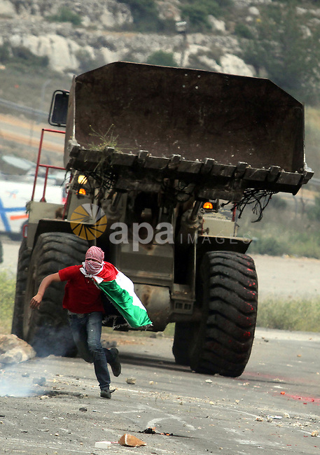 A Palestinian protester runs away from a digger of the Israeli army during clashes to mark Nakba Day outside Ofer military prison near the West Bank city of Ramallah May 15, 2013. Palestinians clashed with Israeli forces in the occupied West Bank and at East Jerusalem on Wednesday during demonstrations to mark 65 years since the Nakba (Catastrophe) when Israel's creation caused many to lose their homes and become refugees. Photo by Issam Rimawi