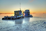 Sunrise behind frozen houseboat Yellowknife Bay.