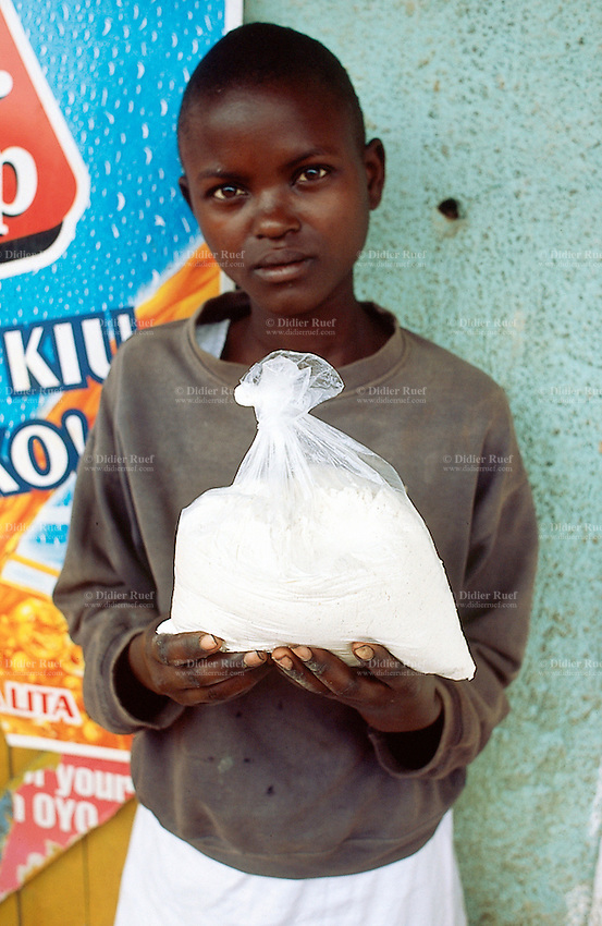 Kenya. Rift Valley Province. Matisi. A young beautiful girl holds in her hands a plastic bag full of maize flour. © 2004 Didier Ruef