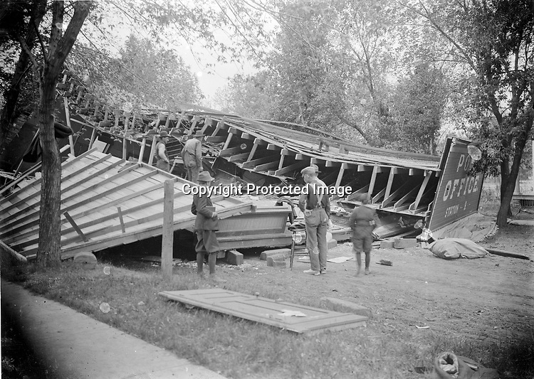 """THE COLLAPSE OF STATION B. Disasters draw gawkers and photographers even more surely than construction sites.  On May 13, 1910, in the process of moving the old S. 17th St. post office to a temporary location while a new substation was built, the frame building collapsed. """"Nothing but a mass of wreckage was left behind.""""  Two postal workers were in the building at the time.  One jumped free unharmed, the other """"had some of his fingers smashed and bruised, but was able to continue his duties afterward.""""<br /> <br /> Photographs taken on black and white glass negatives by African American photographer(s) John Johnson and Earl McWilliams from 1910 to 1925 in Lincoln, Nebraska. Douglas Keister has 280 5x7 glass negatives taken by these photographers. Larger scans available on request."""