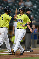 Left fielder Matt Winaker (5) of the Columbia Fireflies is greeted at home by Ali Sanchez (7) after both scored in a game against the Greenville Drive on Friday, May 25, 2018, at Spirit Communications Park in Columbia, South Carolina. Columbia won, 3-1. (Tom Priddy/Four Seam Images)