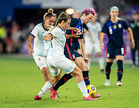 ORLANDO, FL - FEBRUARY 24: Adriana Sachs #21 of Argentina fights for the ball with Megan Rapinoe #15 of the USWNT during a game between Argentina and USWNT at Exploria Stadium on February 24, 2021 in Orlando, Florida.