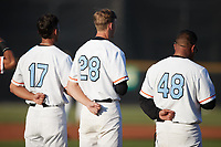 (L-R) Maui Ahuna (17) (Kansas), Chase Johnson (28) (Catawba), and pitching coach Anthony Essien (48) stand for the National Anthem prior to the game against the Danville Otterbots at Burlington Athletic Park on June 5, 2021 in Burlington, North Carolina. (Brian Westerholt/Four Seam Images)