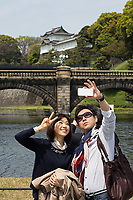 Tourists visiting the Imperial Palace in Tokyo.